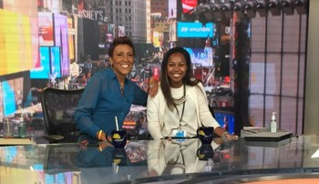 Tiffany Watson sitting next to Robin Roberts on the set of Good Morning America